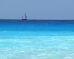 sailboat with a white sail, blue Mediterranean sea
