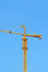 Yellow construction tower crane against blue sky