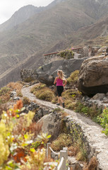 Fitness. Young woman running on a mountain road