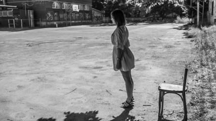 Lonely girl standing in the schoolyard and leaned over horizon
