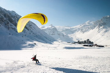 Paraglider landing on skis in Tignes, French Alps