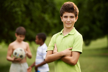Portrait of boy and friends playing football in park