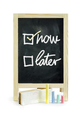 Now or Later,word on blackboard, isolated on white Clipping path
