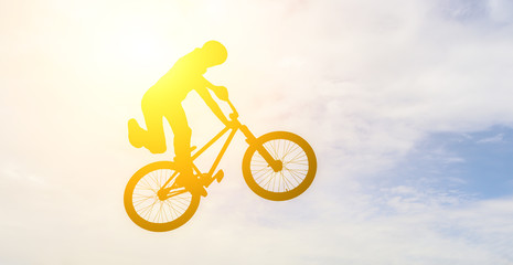 Man doing an jump with a bmx bike against sunshine sky.