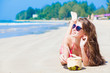 Happy young woman with coconut shake on the beach