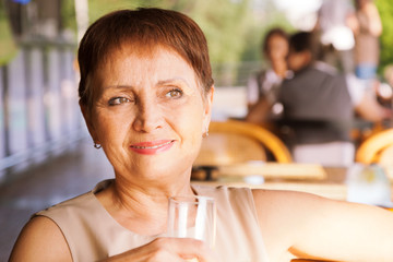 beautiful woman 50 years old with a glass in cafe