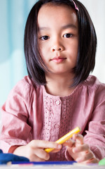 Asian girl with crayons