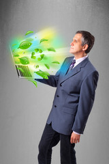 Businessman holding laptop with recycle and environmental symbo
