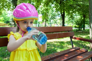 Girl drinking water in the park while resting on a bench