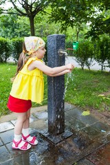 Girl who wash their hands at a fountain in the park