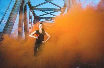 Girl on the old bridge in orange smoke