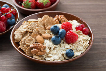 oatmeal and muesli in a bowl, fresh berries on wooden background