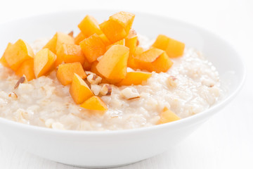 oatmeal with fresh apricots and nuts on a white wooden table