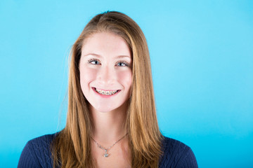 Smiling Beautiful Girl with Braces on Blue Background