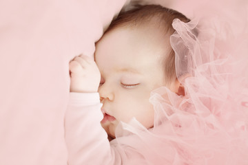 Little girl sleeping on light pink background