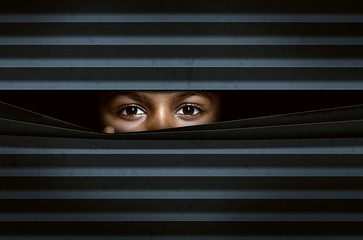 Child looking through window blinds