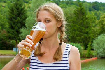 Junge Frau beim Hefeweizen trinken