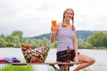Junge, blonde Frau mit Bier