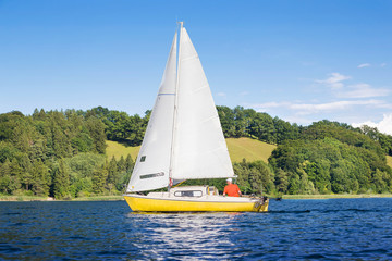 Yellow sail boat on the lake