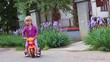 Girl is enjoying in riding her tricycle.