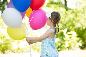 portrait of a happy little girl with baloons
