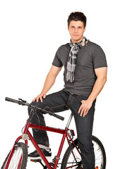 Man with scarf posing seated on a bicycle