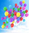 Flying balloons in blue sky with clouds
