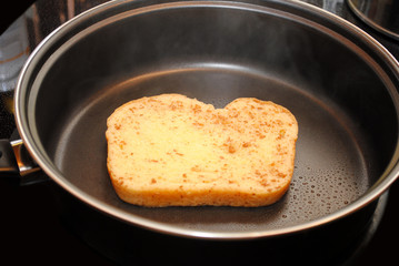 A Sliceof Raw French Toast Cooking in a Fry Pan