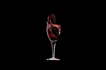 Giochi e schizzi di vino rosso nel bicchiere su sfondo nero