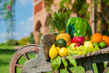 Juicy and colorful fresh fruit arranged on a wooden wheelbarrow