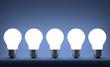 Row of glowing tungsten light bulbs on blue