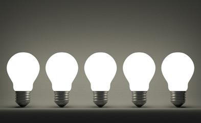 Row of glowing tungsten light bulbs on gray