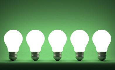 Row of glowing tungsten light bulbs on green