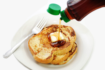 Sweet Maple Syrup Being Poured onto a Plate of French Toast