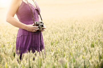 woman retro camera in field