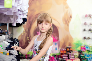 Pretty beautiful girl chooses clothes in shop