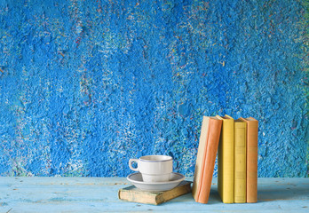 vintage books with a cup of coffee, grungy background, free copy