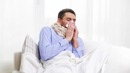 ill man with flu at home sneezing and blowing nose