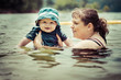 Mother teaching infant baby son to swim in lake
