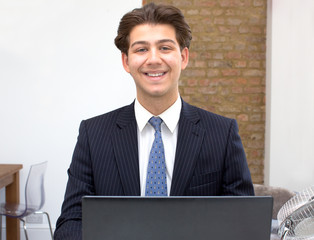 Proud smiling young businessman at his desk
