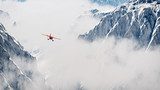 Red airplane flying over snow mountains in the clouds. Aerial sh