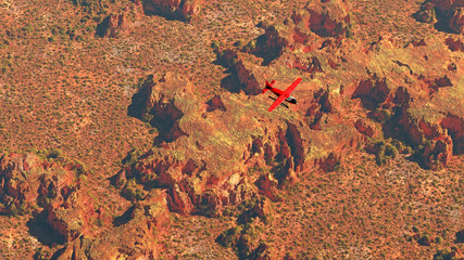 Aerial of red airplane flying over dry red desert landscape.
