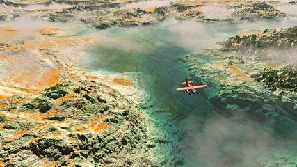 Aerial of red airplane flying over rocky landscape with river an