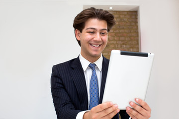 Elated businessman reading good news on a tablet