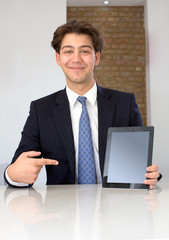 Pleased businessman pointing at a blank tablet