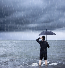 upset business man holding a umbrella with cloudburst background