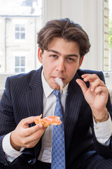 Young man smoking while eating a snack