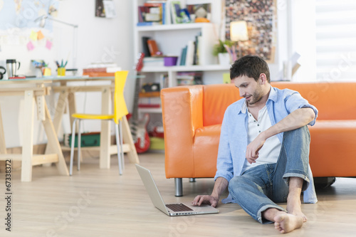 young student works on his laptop at home - 67338372