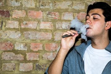 Young man enjoying a satisfying e-cigarette