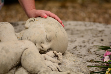 Baby loss - mum's hand on memorial statue